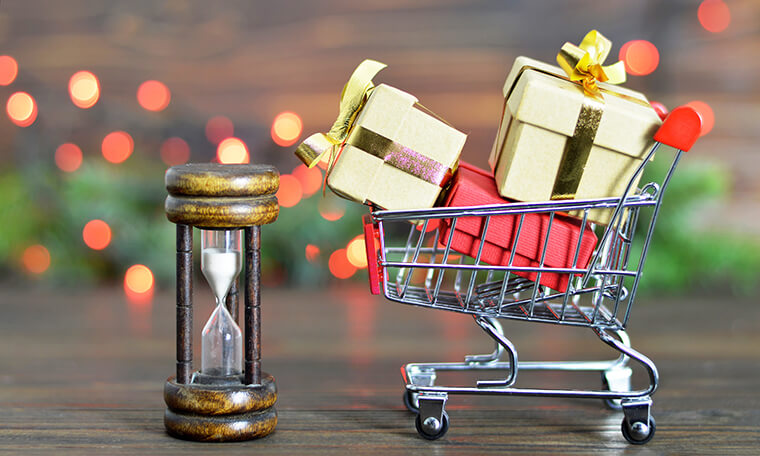 Photograph depicting the holiday rush as a cart full of miniature gifts running into an hourglass.
